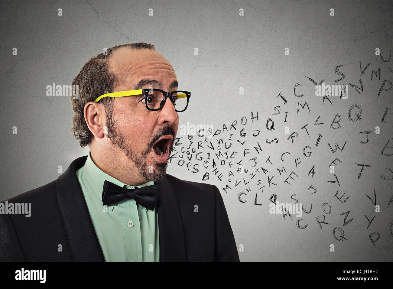 Side view portrait middle aged business man talking with alphabet letters coming out of open mouth isolated grey - Stock Image