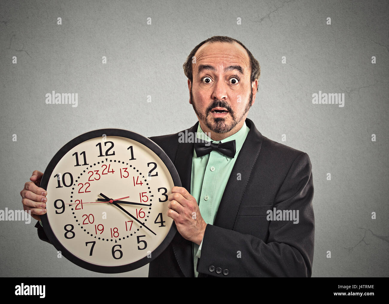portrait surprised business man in suit holding wall clock isolated grey wall background. Race against time, time - Stock Image
