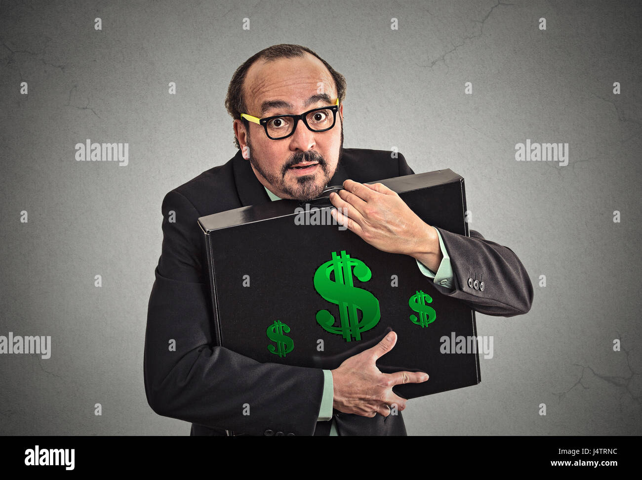 Money greed wealth security. Wealthy business man in suit holding holding hugging tight case full with dollars money - Stock Image