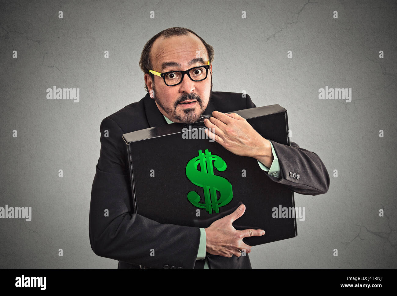 Money greed. Business man holding holding case with dollars tightly isolated on grey wall background. Worship, miser, - Stock Image