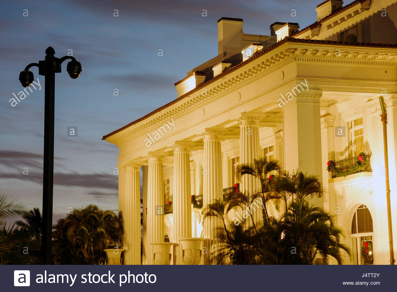 Palm Beach Florida Flagler Mansion Museum historic landmark Guilded Age building exterior lighted dusk column Beaux - Stock Image