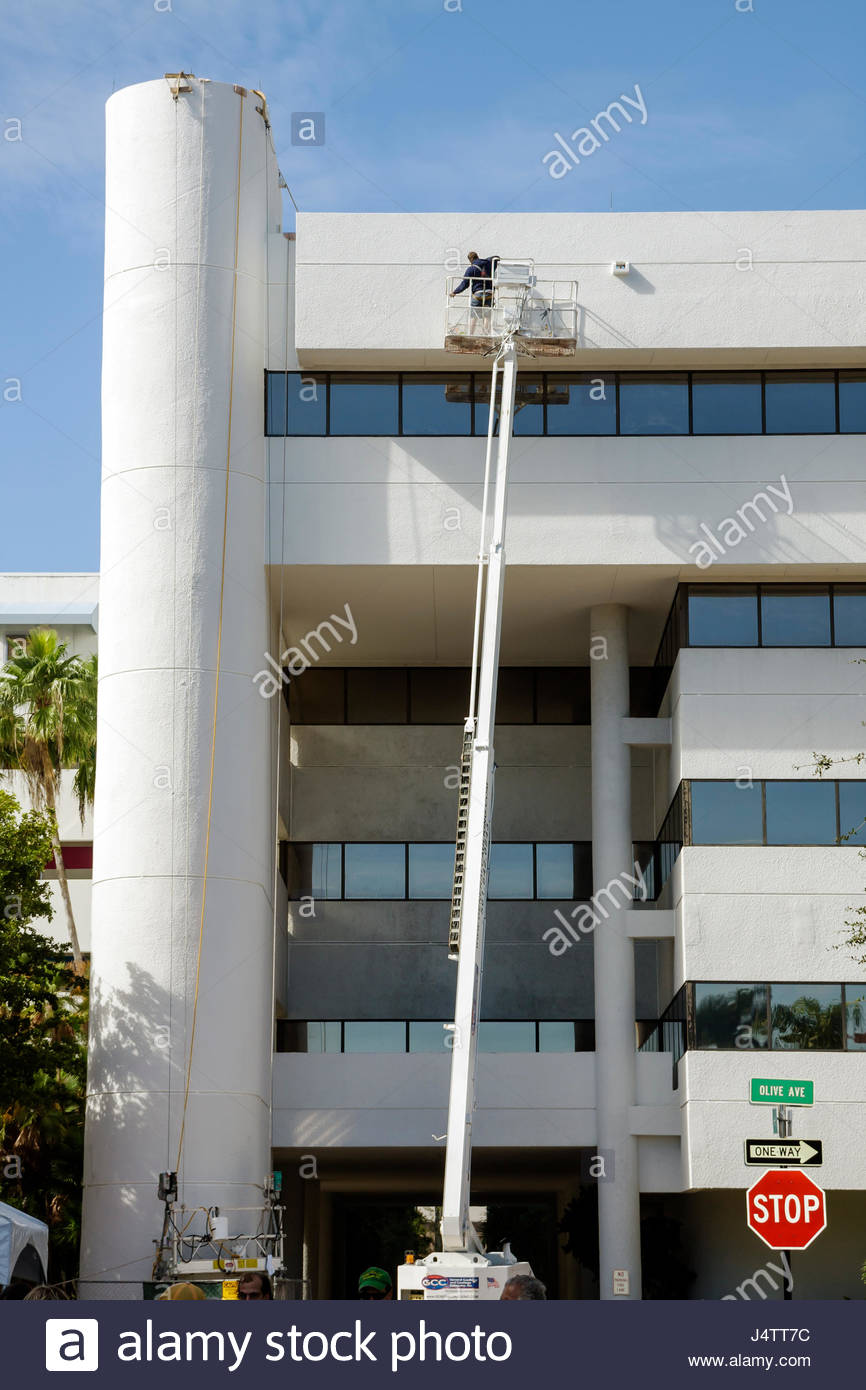West Palm Beach Florida Olive Avenue office building multi story exterior man worker job repair cherry picker boom - Stock Image