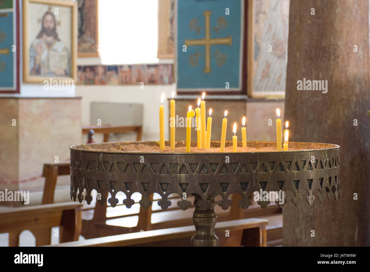Lit Candles in the Church of St George, Madaba, Jordan in a large metal candle holder on a pedestal. Iconography - Stock Image