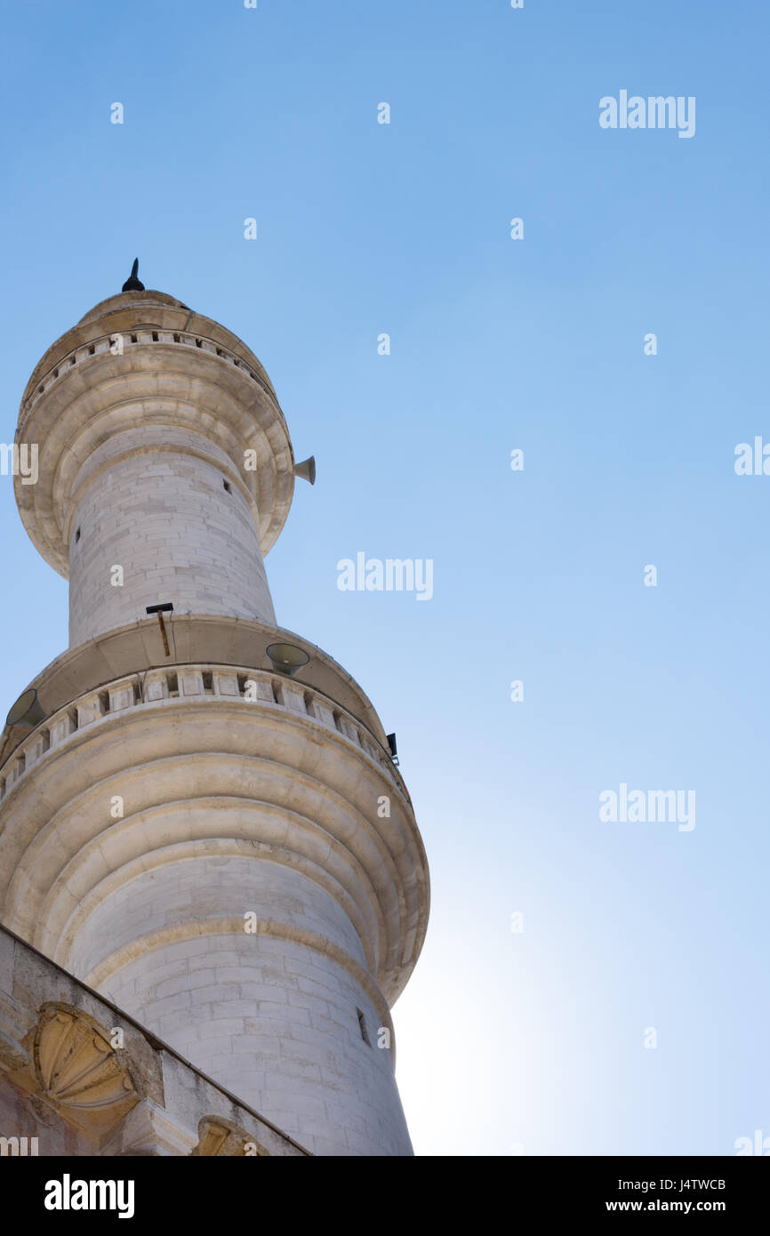 White stone minaret in Amman Jordan photographed from below with clear blue sky above. It has loud speakers for - Stock Image