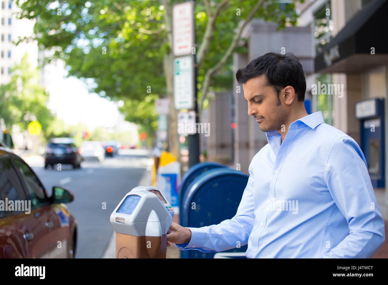 Closeup portrait, young man in blue button down shirt putting coins in parking meter outside to prevent fines, isolated - Stock Image