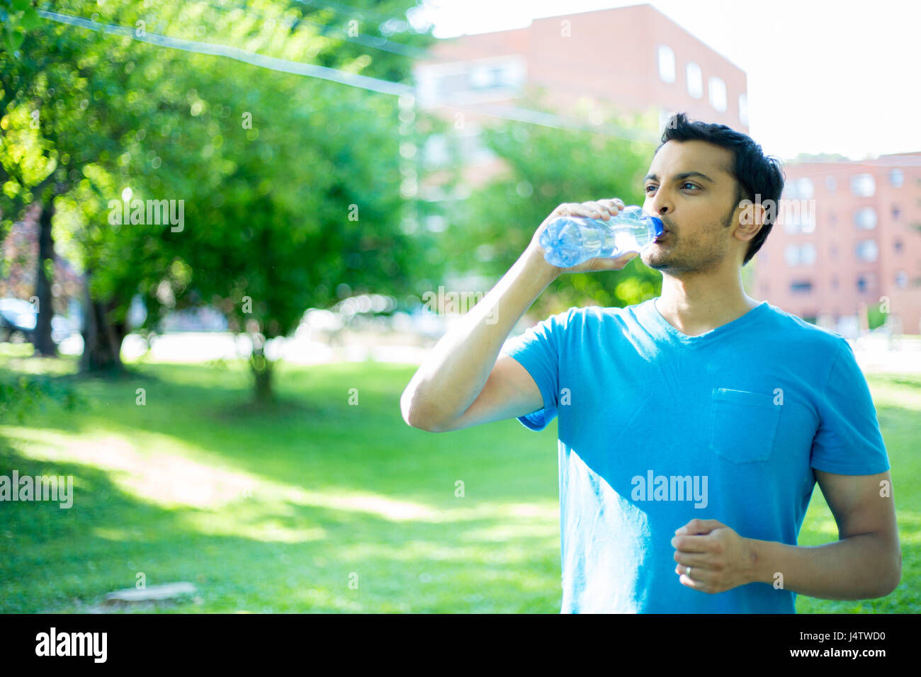 Closeup portrait of young guy in blue shirt drinking water from crystal clear bottle on a hot, sunny day, isolated - Stock Image
