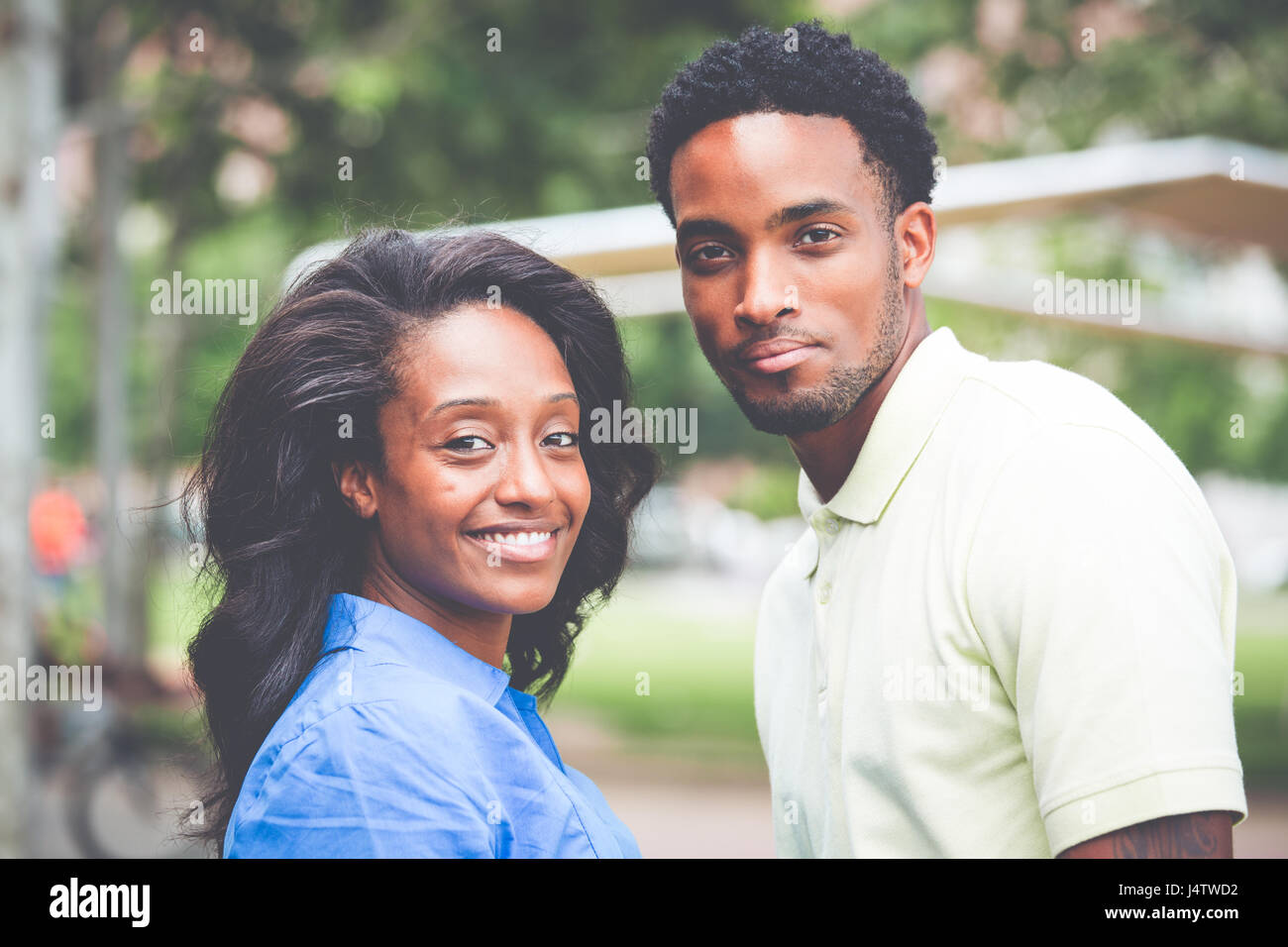 Closeup portrait of a young couple, guy in yellow shirt holding woman with blue shirt, happy moments, positive human - Stock Image