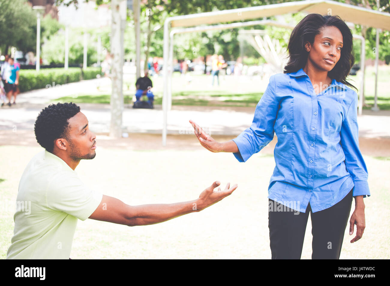Portrait of young woman showing talk to hand gesture to desperate man hoping to persuade her to see his point. Please - Stock Image