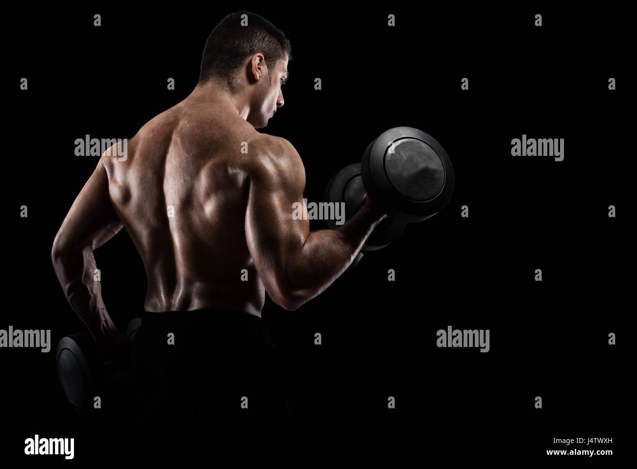 Athletic man training biceps on black background - Stock Image