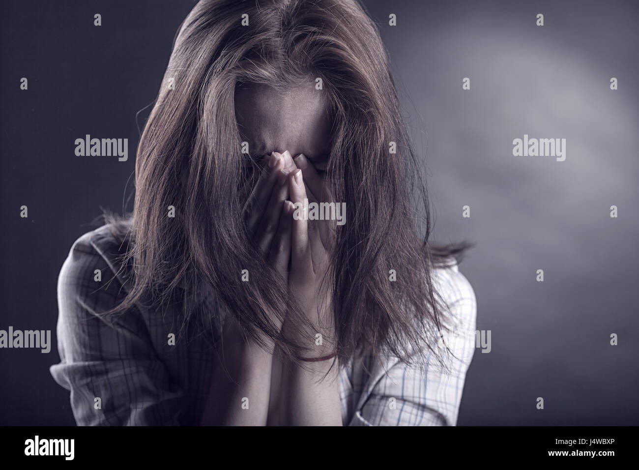 Young woman crying face in her hands on a dark background - Stock Image