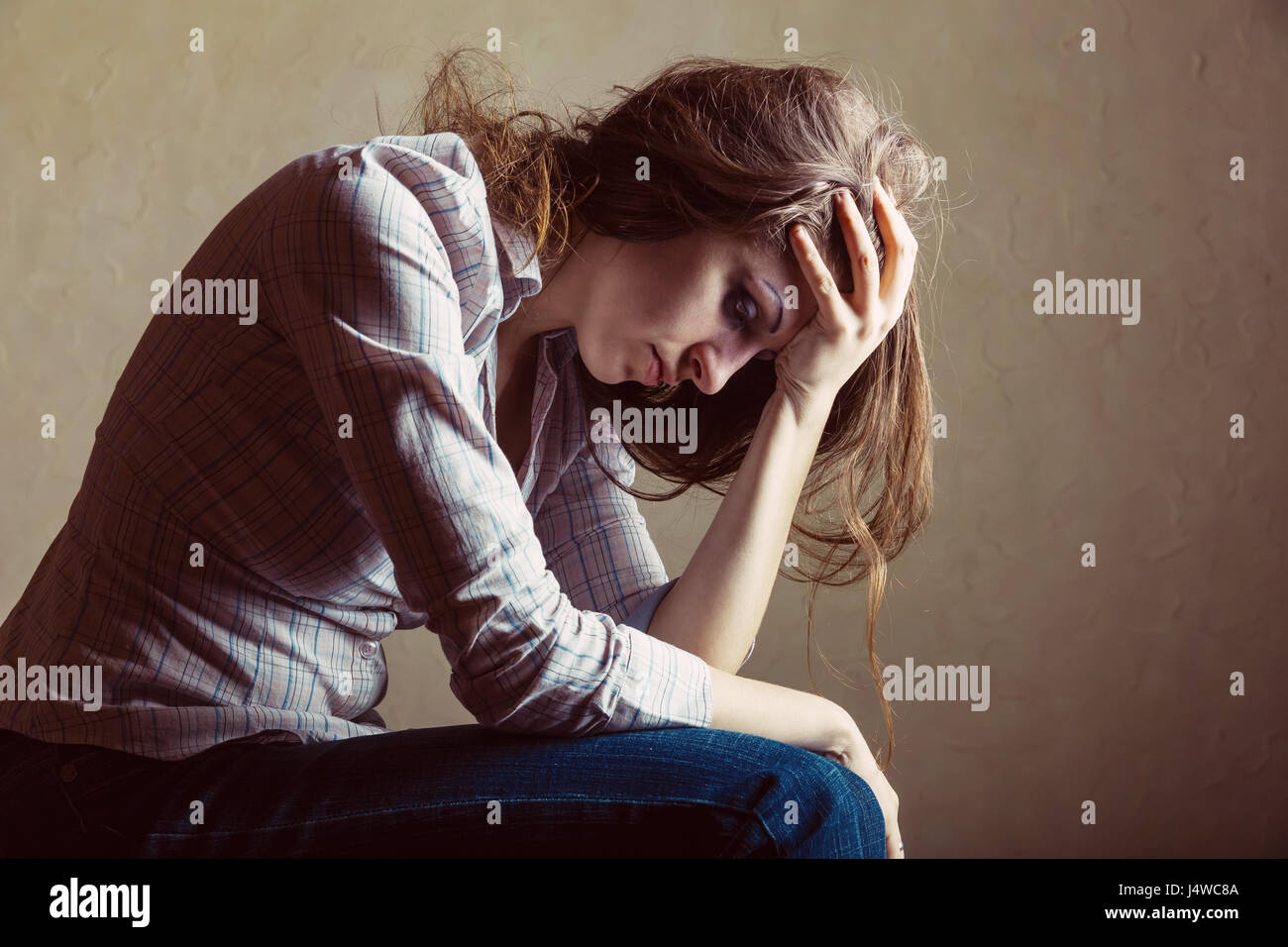 Young sad girl sitting alone in an empty room - Stock Image