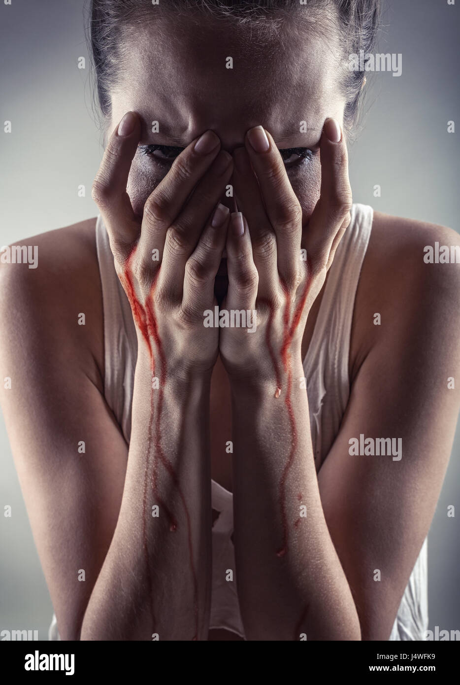 Crying woman with his hands in the blood - Stock Image