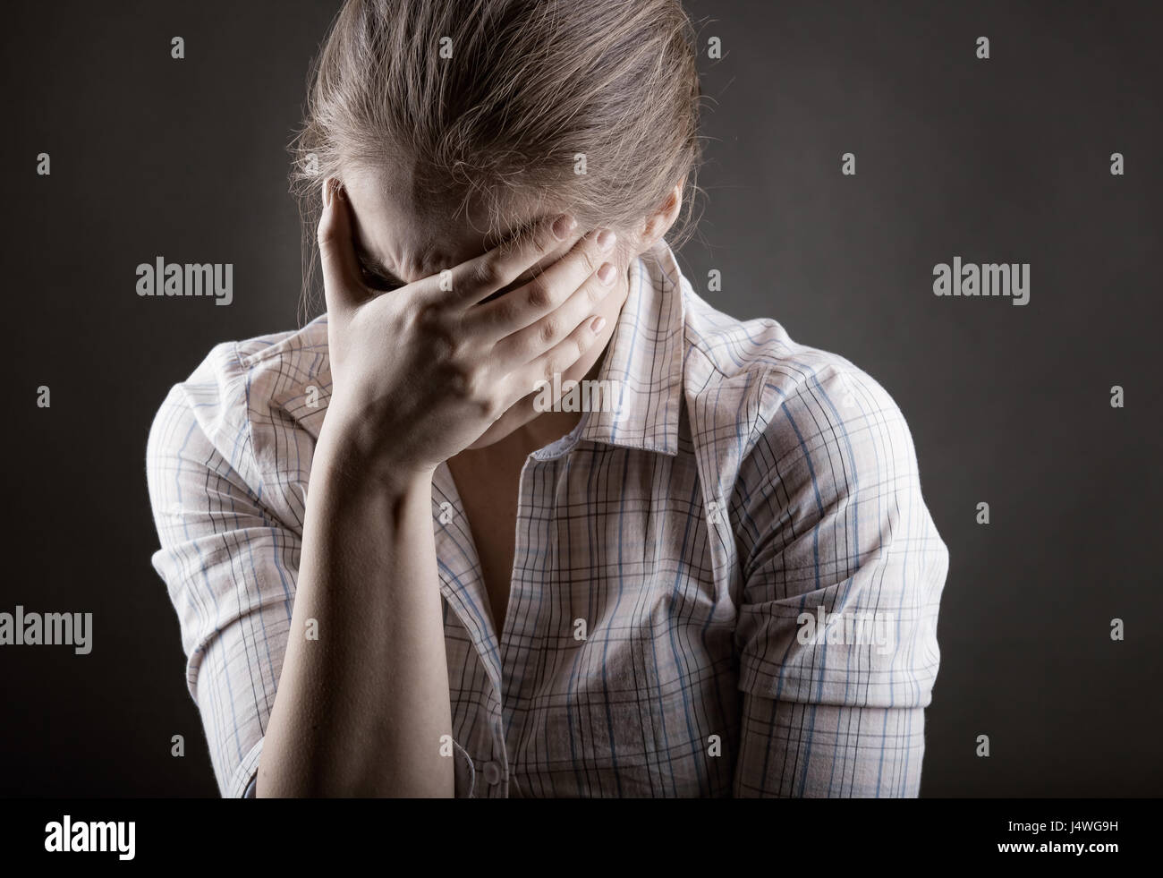 Young crying woman on a dark background - Stock Image