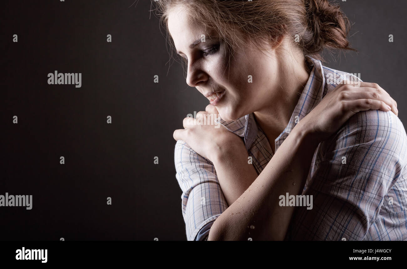 Young woman desperately crying on a dark background - Stock Image