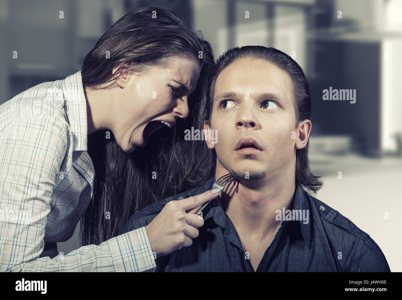 Family quarrel. Young woman stabs husband's throat - Stock Image