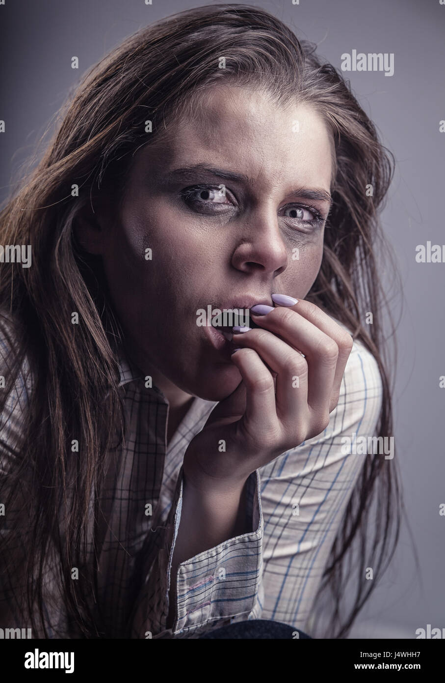 Young frightened woman with tearful eyes on a gray background - Stock Image