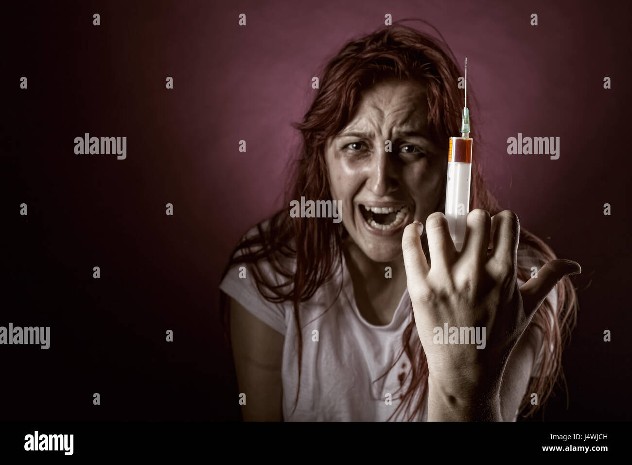 Weeping Woman addict. Focus on the syringe - Stock Image
