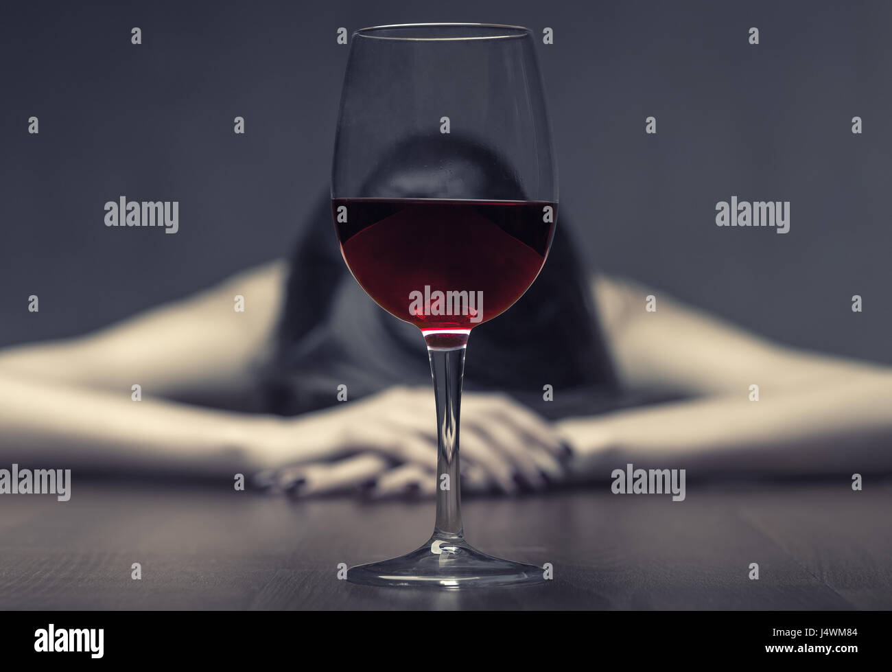 Woman in depression, drinking alcohol on dark background. Focus on the glass - Stock Image