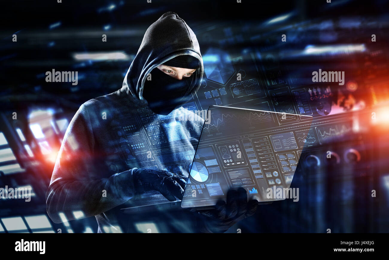 Computer Hacker In Hoodie And Mask Stealing Data From Laptop