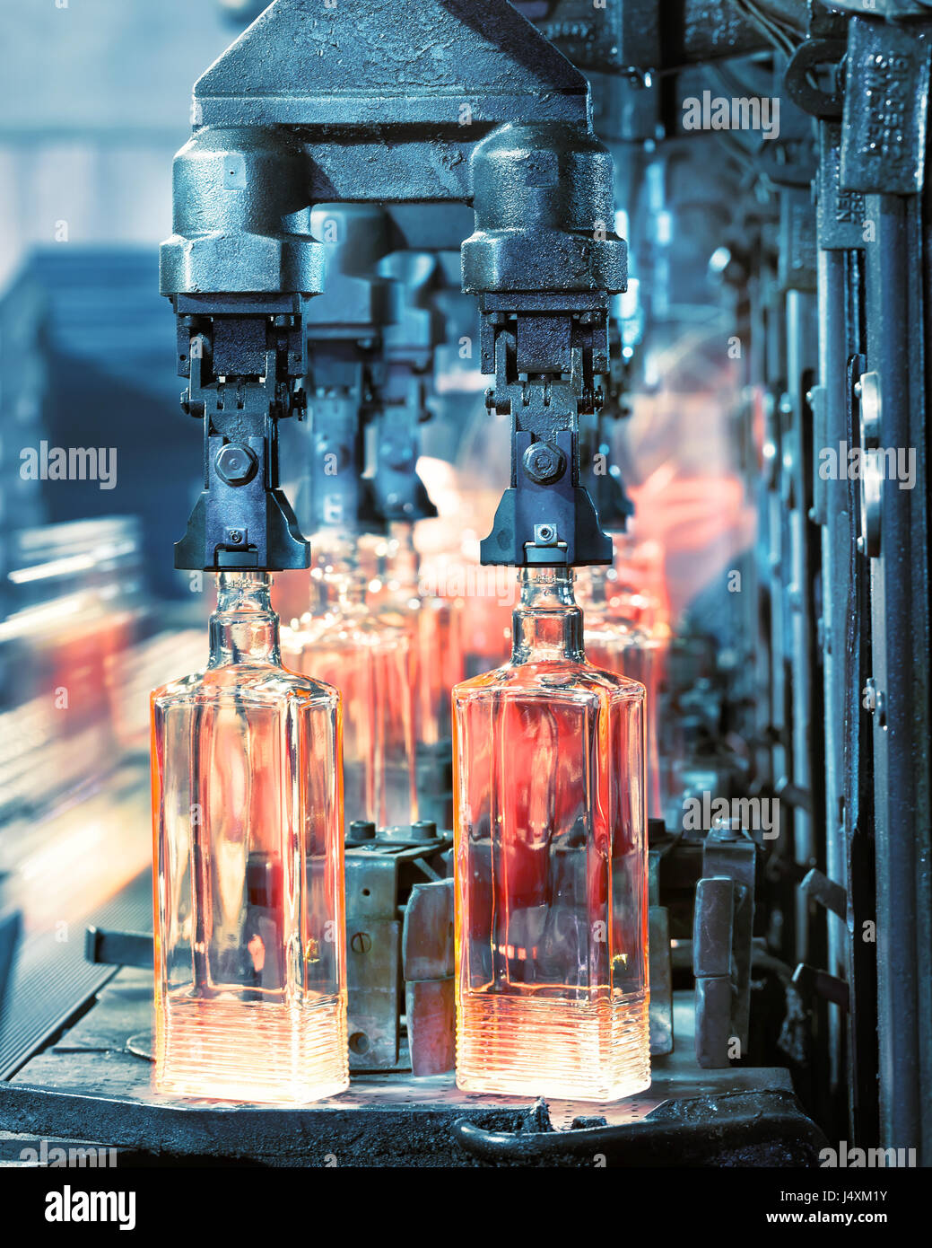 The machine for the production of glass bottles in the production process is tinted in blue - Stock Image