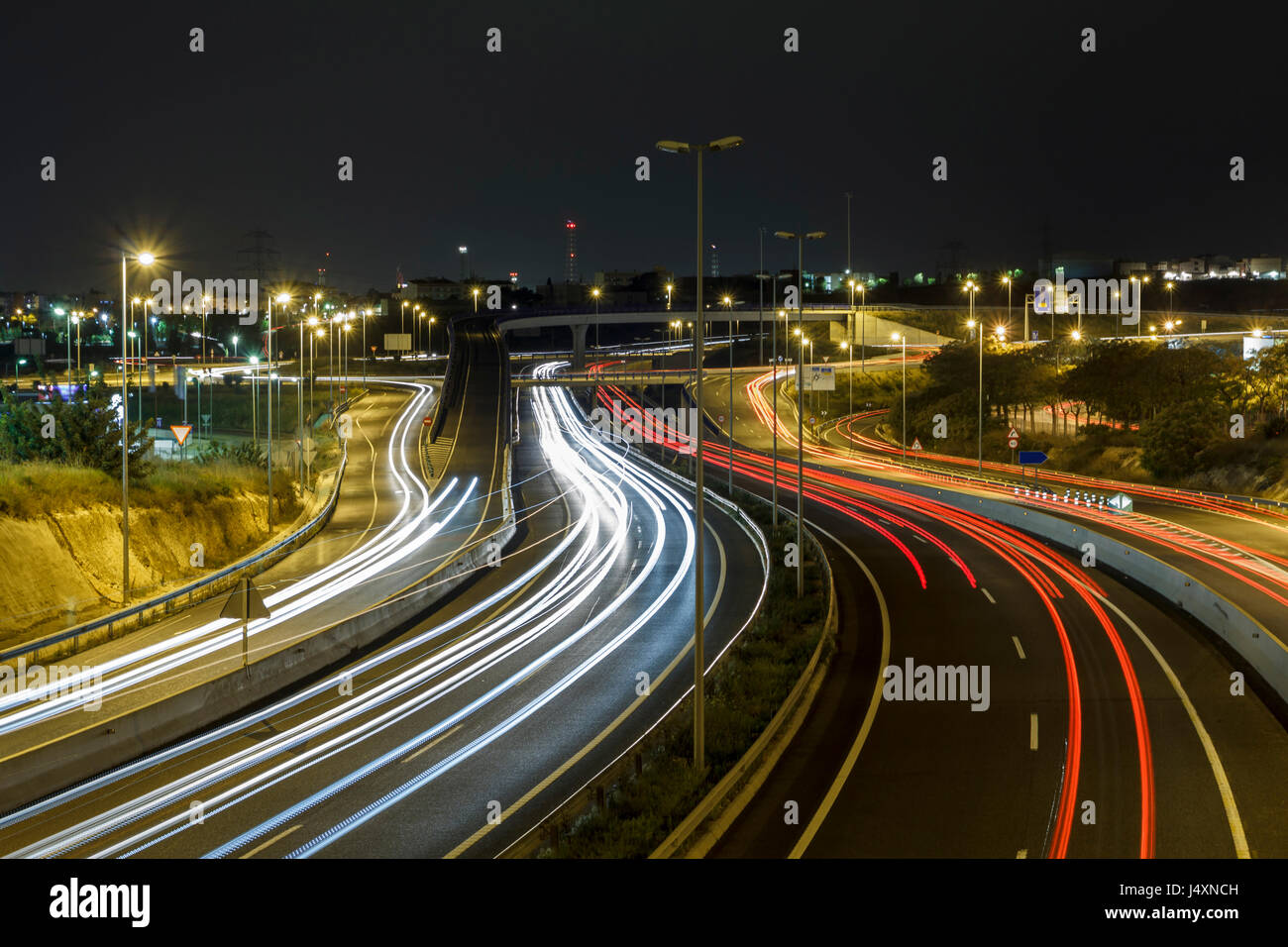 Long exposure shot of highway at night, with cars driving in the road - Stock Image