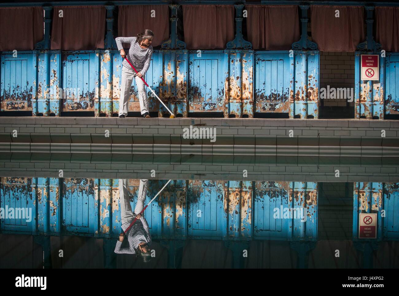 A woman mops the floor at Victoria Baths in Manchester, ahead of their open swim day to raise funds for restoration - Stock Image
