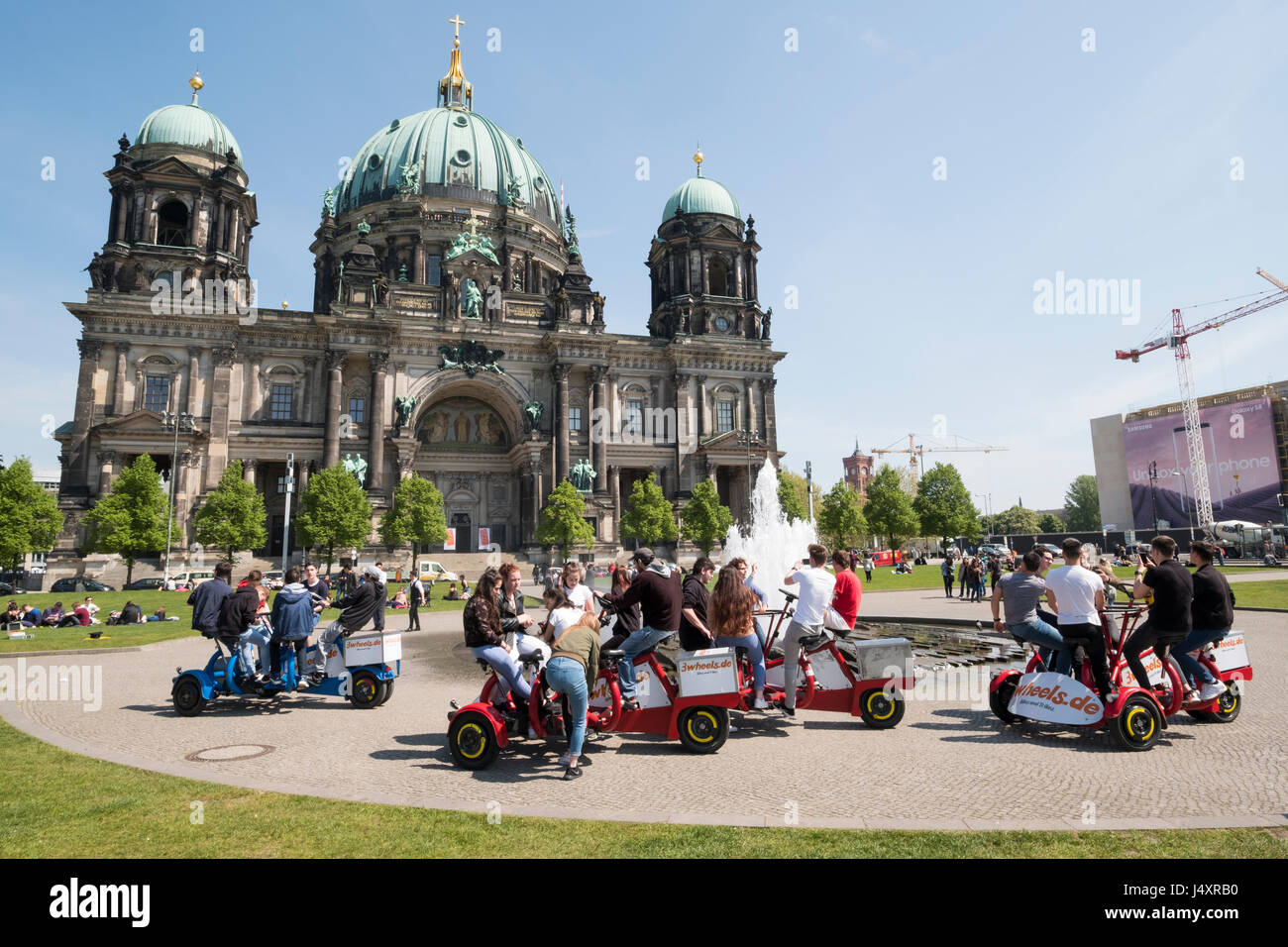 Berlin Cathedral and Lustgarten with tourists on team bikes, Berlin, Germany - Stock Image