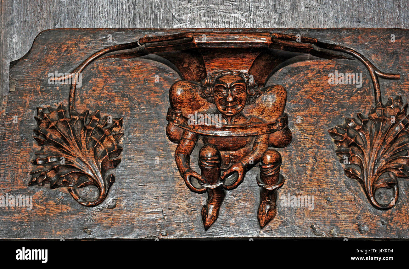 Misericord ni Parish church of St Laurence, Ludlow.  Portern or Pedlar pulling on boot with a pack, possibly woollen - Stock Image