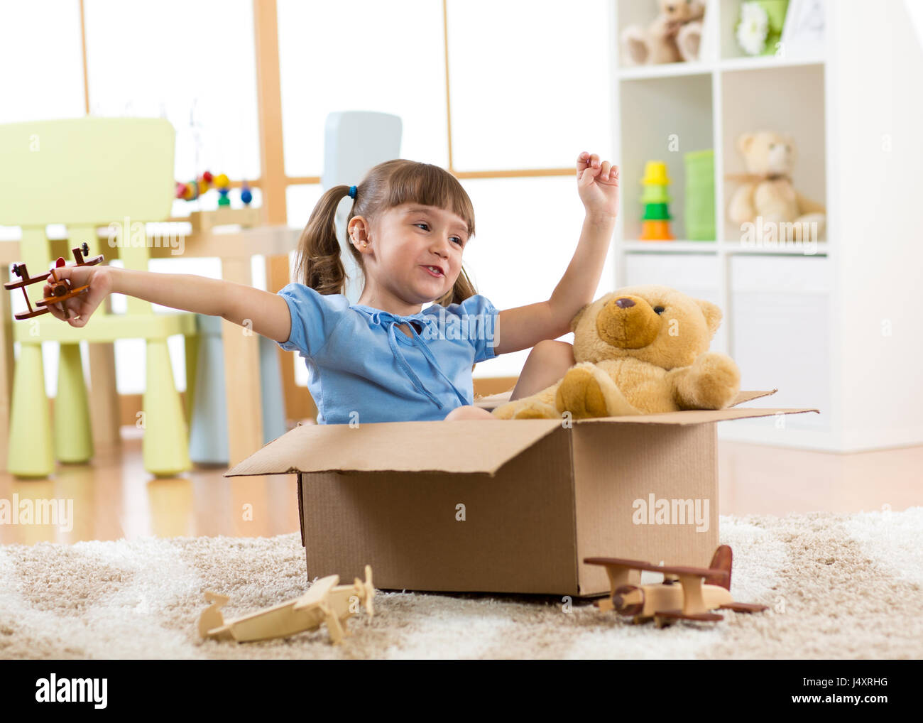 Child playing with plane toy at home. Travel, freedom and imagination concept. Stock Photo