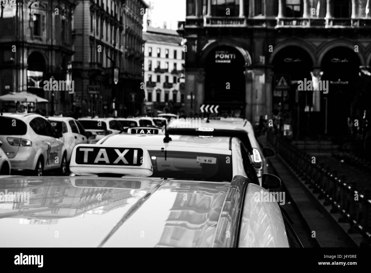 view of taxy parked in a row on a street in milan - Stock Image