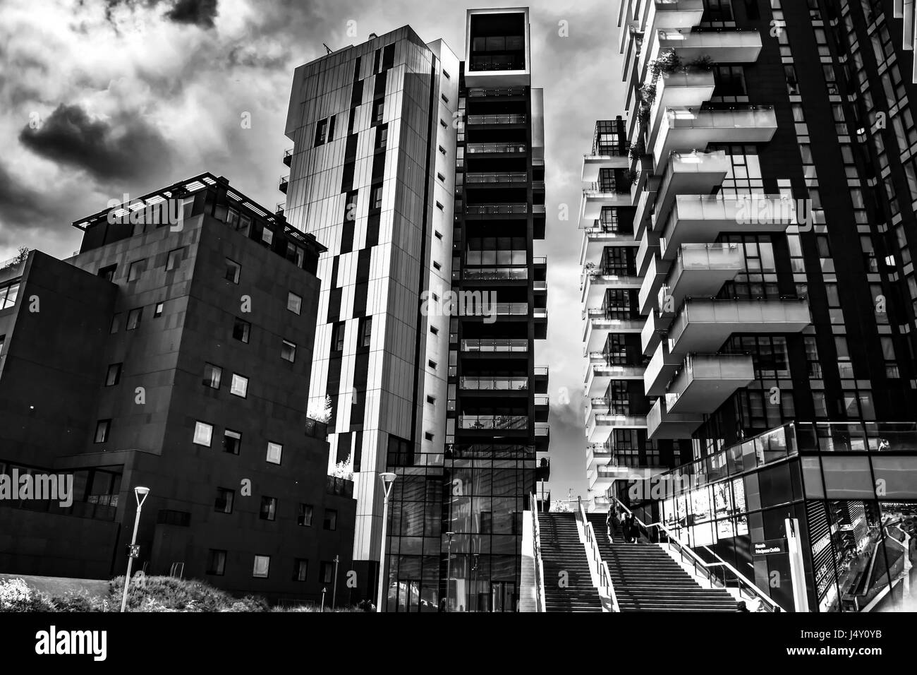 A black and white photography of modern buildings architecture in milan dowtnown with a cloudy sky on background