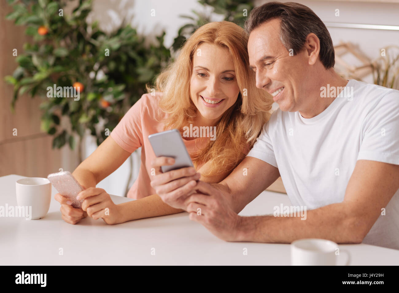 Cheerful couple using digital gadgets at home - Stock Image