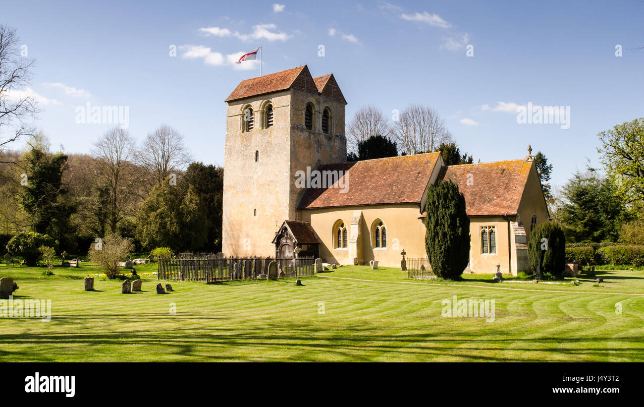 Sun shines on the tower of the 12th century Norman church of St Bartholomew in the village of Fingest, nestled under - Stock Image