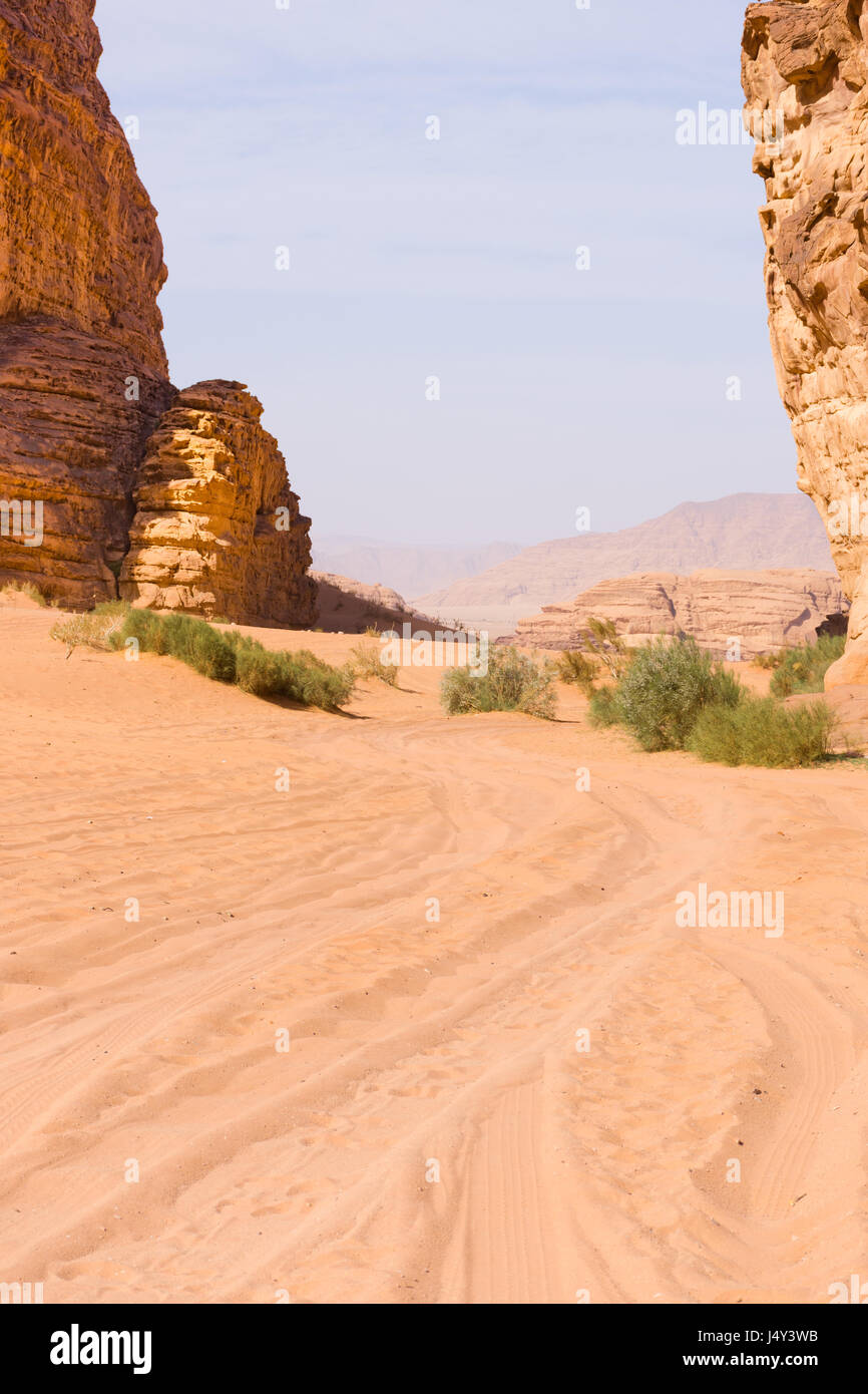 Four wheel tracks through orange, rose colored sand of the Wadi Rum Desert in Jordan. Blue sky is above and sparse - Stock Image
