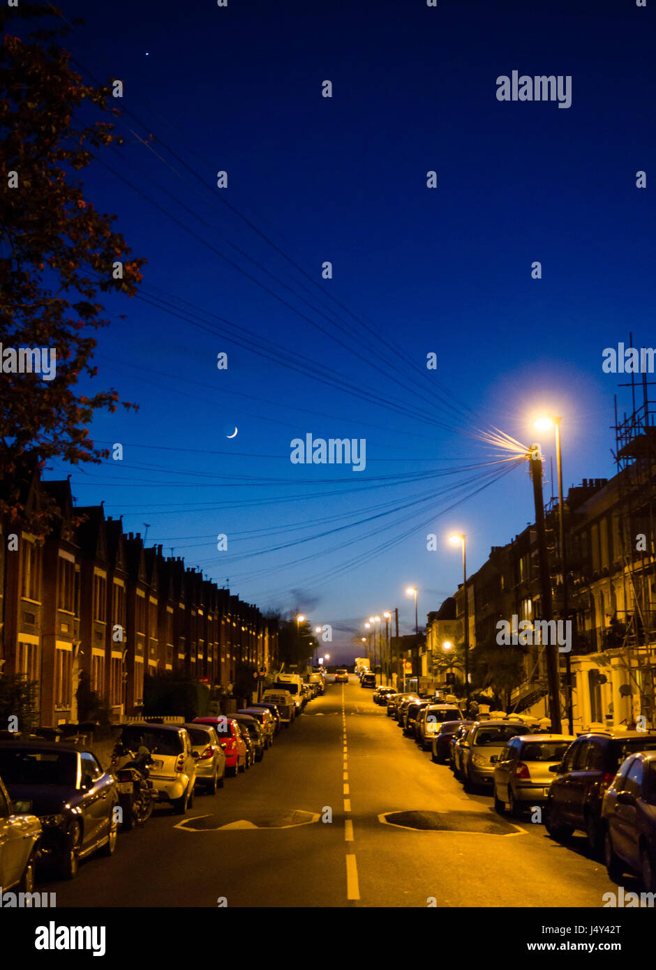 London, England, UK - April 20, 2015: The moon rises above traditional suburban terraced houses and parked cars - Stock Image