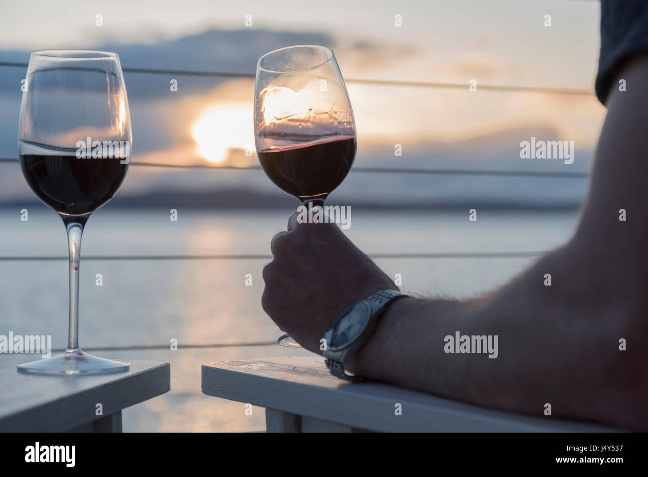 Couple enjoying seaside sunset with crystal glasses of red wine Stock Photo
