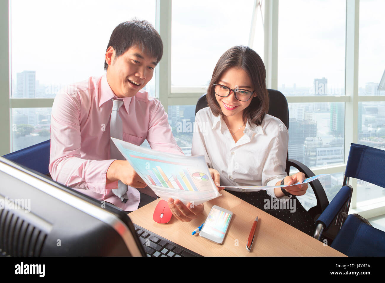 younger man and woman meeting in office working table scene for people business lifestyle - Stock Image
