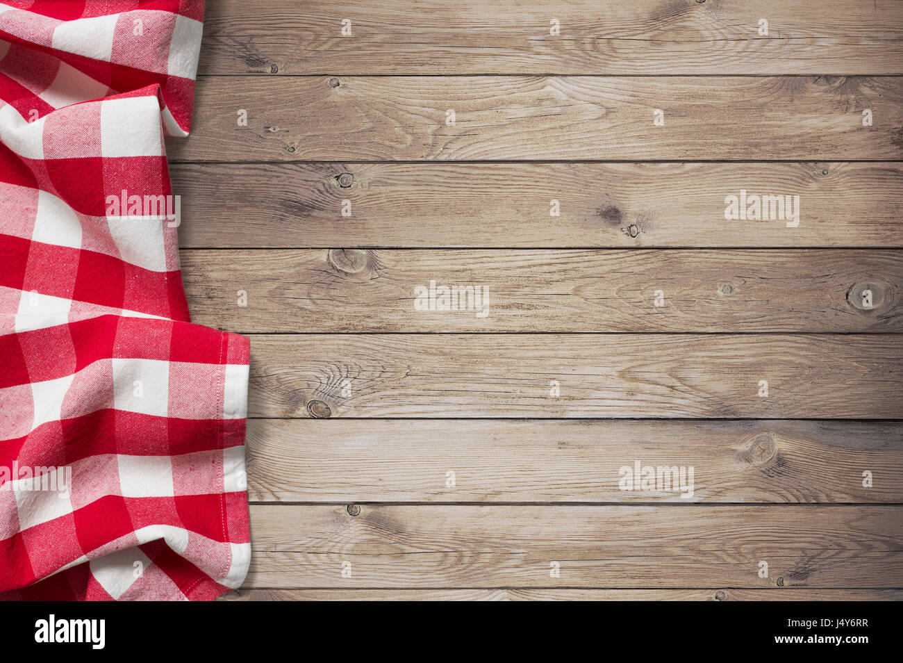 red picnic tablecloth on wood table background Stock Photo