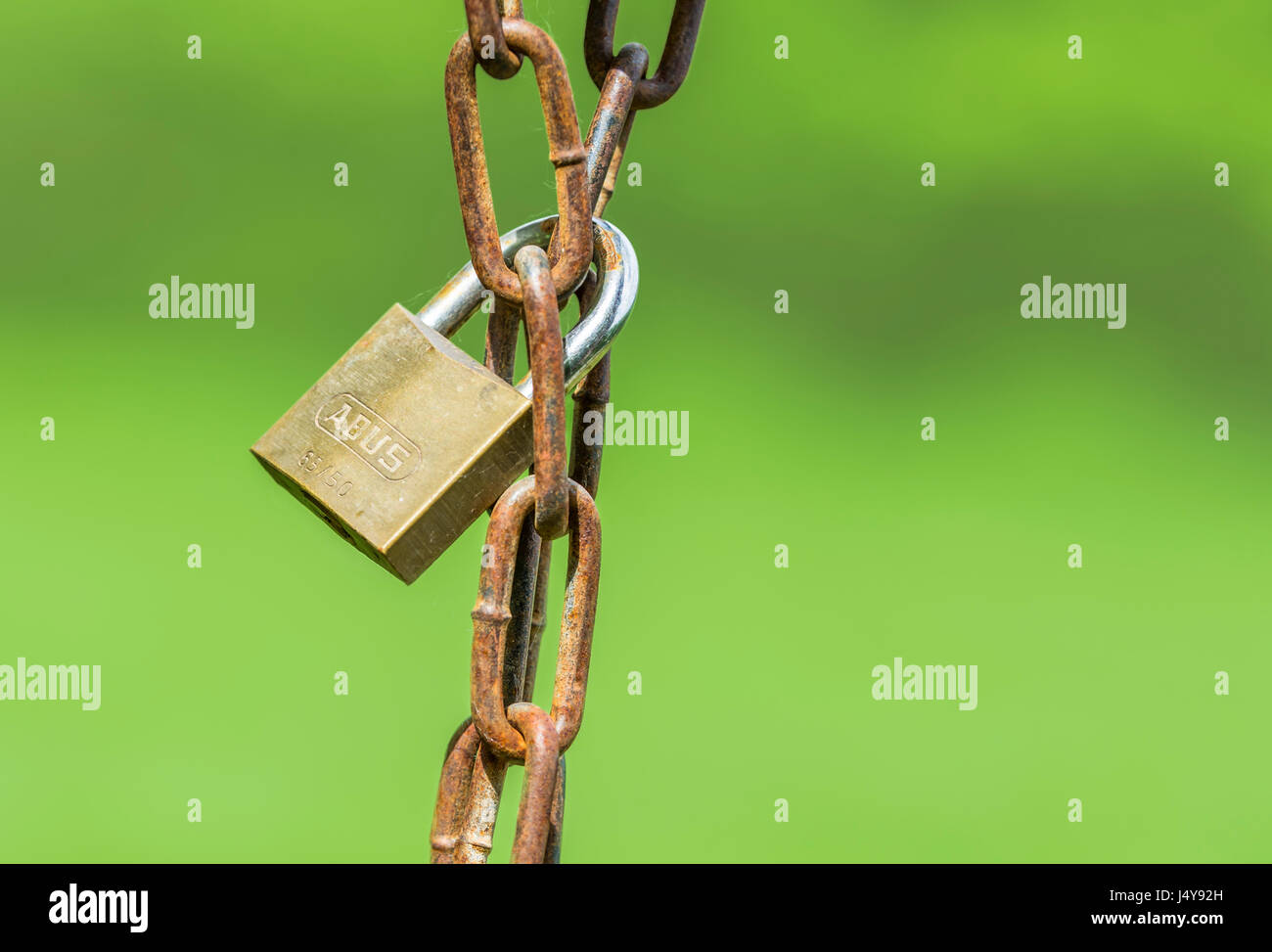 Locked concept. Locked padlock around a rusty chain. Lock hanging from a chain. - Stock Image