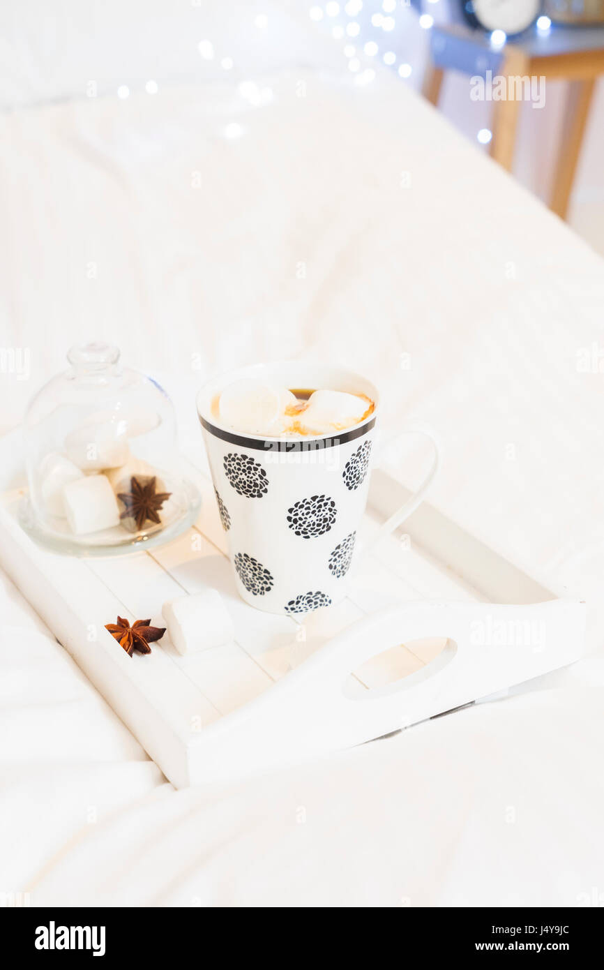 Breakfast in bed - tray with cup of coffee and marshmallows, cozy hygge home style - Stock Image