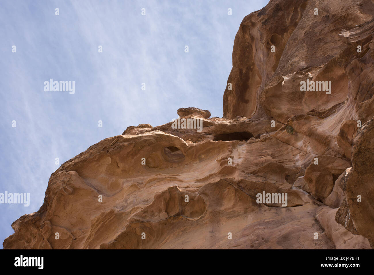 The steep sandstone walls of a natural mountain fault that leads to the Treasury, Al Khazneh, in Petra, Jordan. Stock Photo