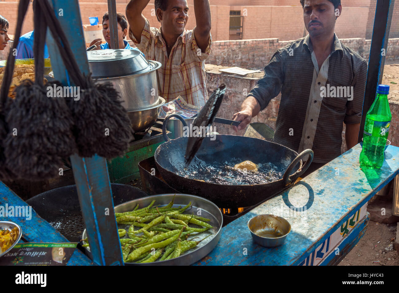 Jodhpur, India - 19 November 2012 - Street vendor fries the food for waiting customers, a very popular way of eating - Stock Image