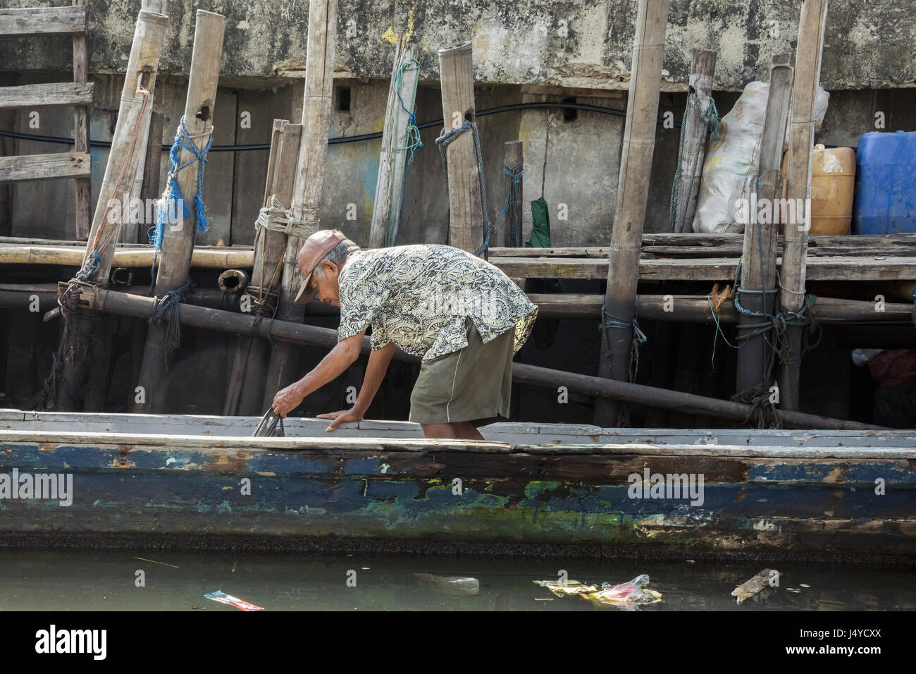 An old man in a ball cap retrieves a bag of goods from the bottom of his old wooden canoe by one of the bamboo walkways - Stock Image