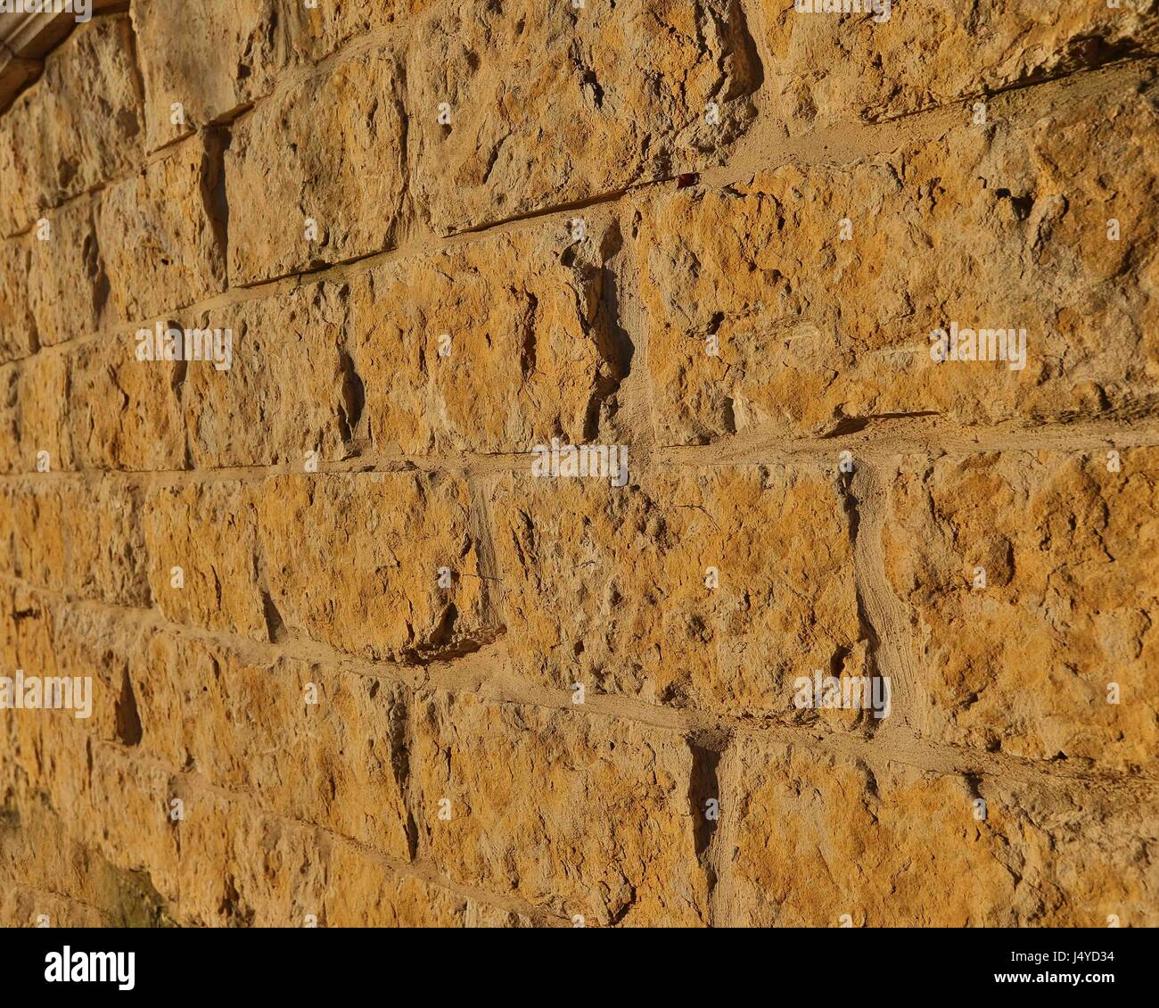 Stone Wall in warm colors for backgrounds - Stock Image
