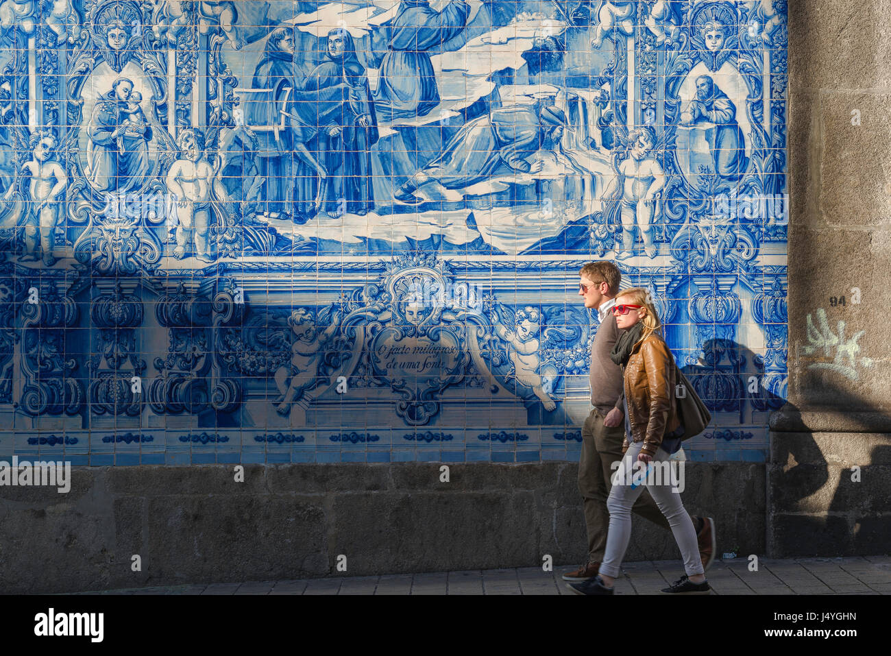 Portugal tiles people, a young couple walk past a wall of blue azulejos tiles on the side of the Capela das Almas - Stock Image