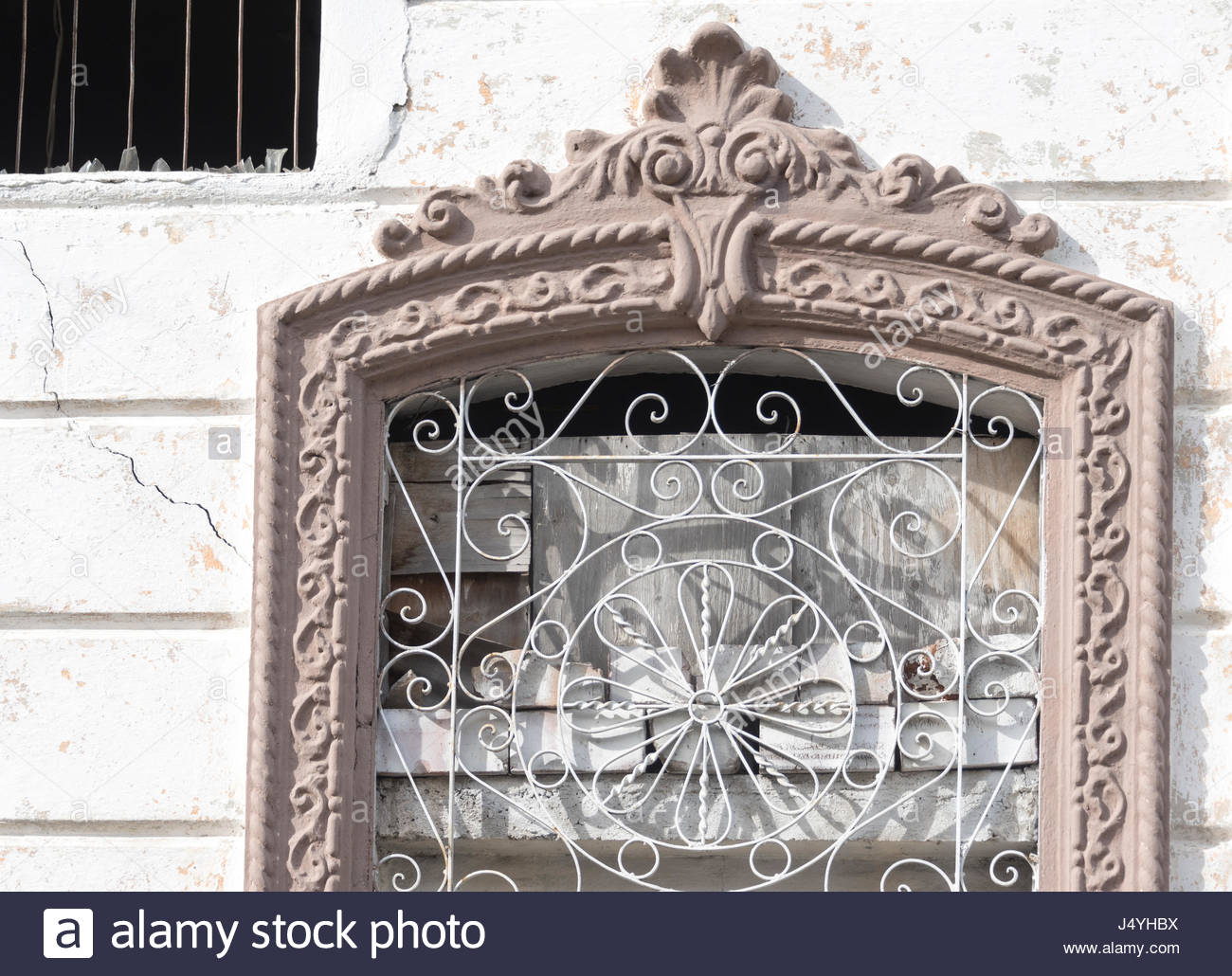 Cuban old weathered and worn out architecture. Highe decorated window in house, details. Results of economic hardship - Stock Image