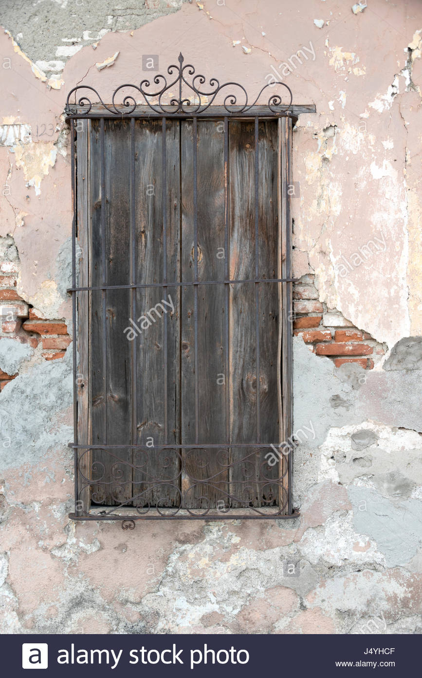 Cuban old weathered and worn out architecture. Colonial wooden window with iron guard.  Results of economic hardship - Stock Image