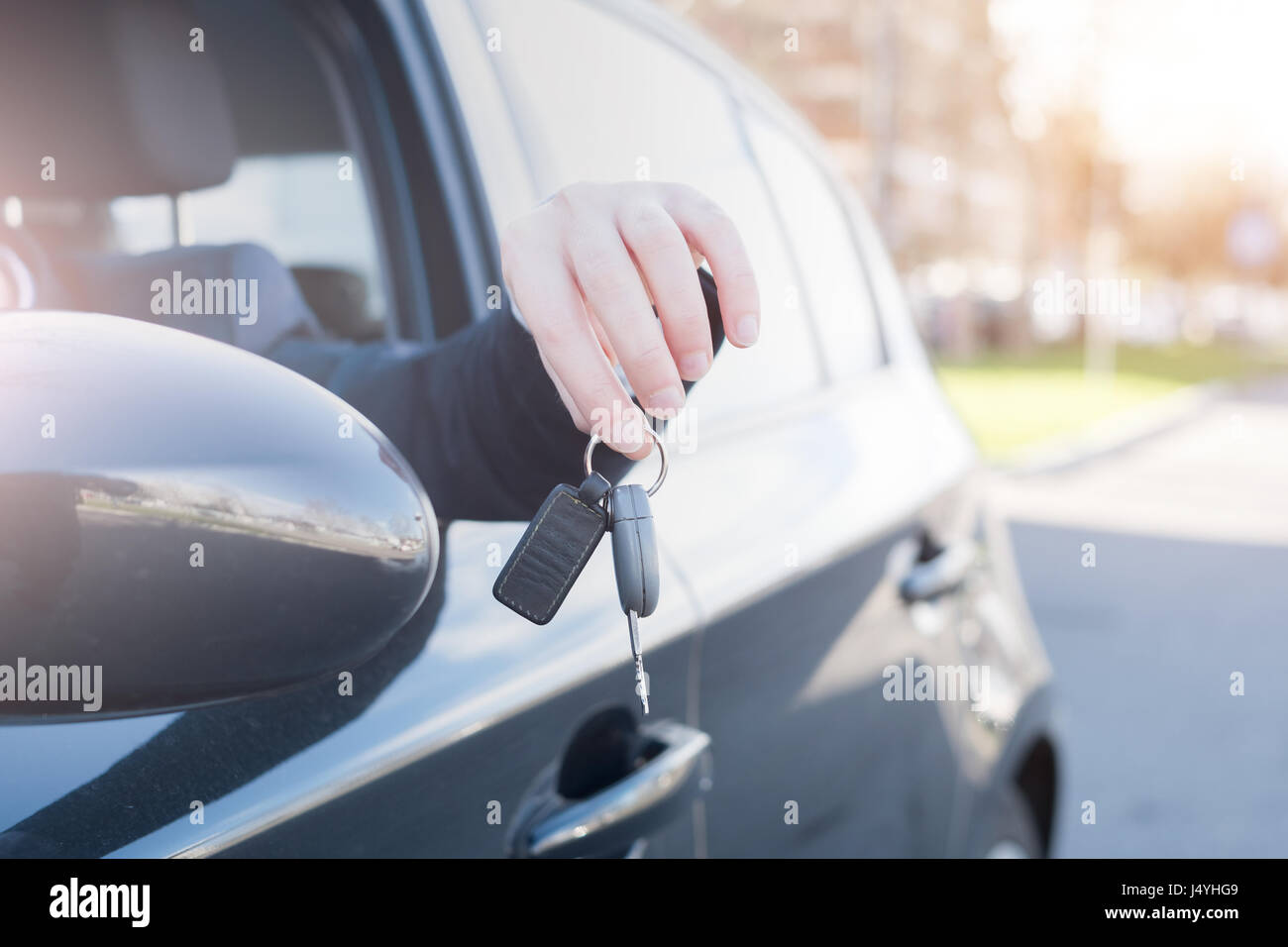 Man seated in his car holding the key - Stock Image