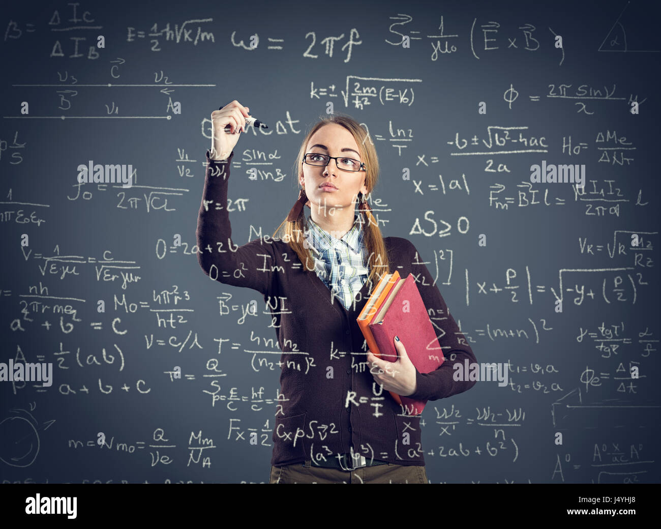 Student girl writing formulas on transparent wall front her - Stock Image