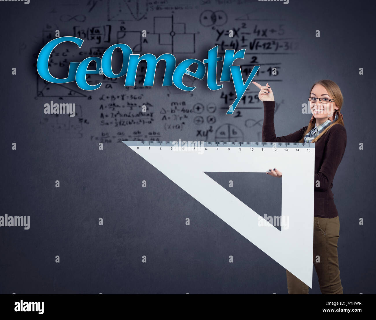 Student girl pointing at word geometry and holding big triangle ruler - Stock Image